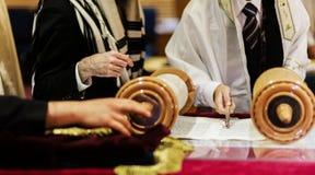 Hand av pojken som läser den judiska Torahen på bar mitzwah Royaltyfria Bilder