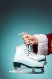 Hand av Santa Claus som rymmer ett diagram skridskor på blå bakgrund Royaltyfri Foto