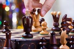 Hand av schackspelaren med drottningen Royaltyfri Fotografi