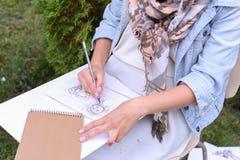 Hand av slaglängder för flickakonstnärMakes Sure Sharp blyertspenna på albumet Pag royaltyfri fotografi