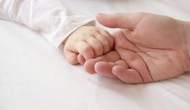 Hand av sonen och stor hand av farsan Fotografering för Bildbyråer