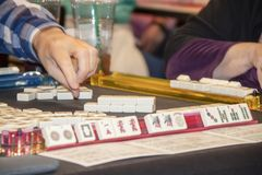 Hand av spelaren som når för tegelplatta i en lek av Mahjong - selektiv fokus arkivbilder