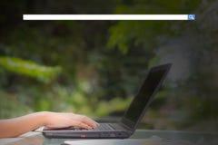 Hand av ung maskinskrivning för affärskvinna genom att använda digital information om bärbar datordator med den tomma sökandestån royaltyfri foto