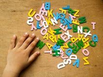 Hand av ungen med färgrika wood alfabet royaltyfri fotografi