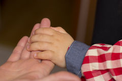 Hand of a baby. Baby hand gently holding adult's finger Stock Photo