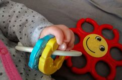 Hand of baby laying on back, holding toy stock photos