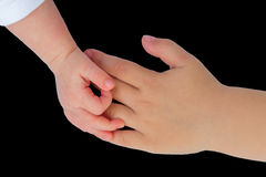 Hand of baby touching hand of child on black Royalty Free Stock Photo