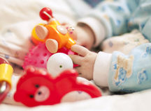 Hand with baby toys Stock Photo