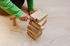 Hand of baby who played developmental game of wooden blocks Stock Photo