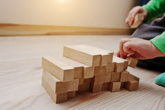 Hand of baby who played developmental game of wooden blocks. Lumber Royalty Free Stock Images