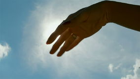 Hand in backlight of sun stock video