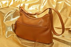 Hand Bag. Ladies Brown hand bag on golden background Stock Photo