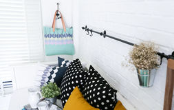 Hand bag hung on the white brick wall with colorful pillows Royalty Free Stock Photography