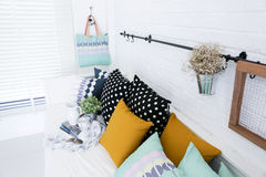 Hand bag hung on the white brick wall with colorful pillows Stock Photos