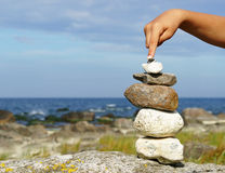 Hand balancing pile of stones Royalty Free Stock Photo