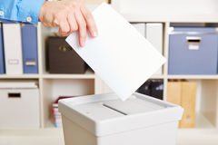 Hand with ballot paper. And election booth in polling station Stock Photo