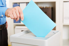 Hand with ballot paper during election. Hand with ballot paper an voting booth during election Royalty Free Stock Photo