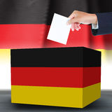 Hand with ballotand box on Flag of Germany Stock Photo
