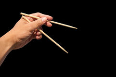 Hand and bamboo chopsticks. Use left hand to eat food with chopsticks stock image