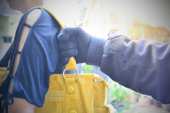 Hand of bandit steal bag another person in the public under the Royalty Free Stock Image