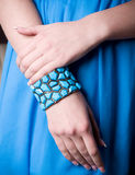 Hand in bangle on blue Royalty Free Stock Photos