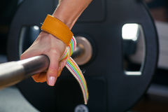 Hand on the barbell. Young athlete getting ready for weight lifting training carpal bandage Royalty Free Stock Photos