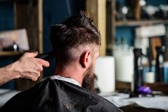 Hand of barber with hair clipper close up. Hipster bearded client getting hairstyle. Barbershop concept. Man with beard. In hairdressers chair, salon background royalty free stock image