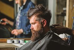 Hand of barber with hair clipper, close up. Hipster bearded client getting hairstyle. Barbershop concept. Man with beard. In hairdressers chair, salon stock photos