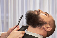 Hand of barber trimming beard. Royalty Free Stock Photography
