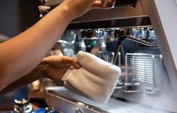 Hand of barista cleaning milk frother of coffee machine to be ready for milk frothing royalty free stock photo