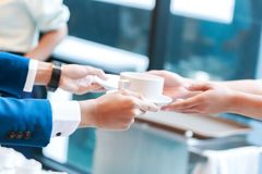 Hand barista hold cup of coffee and send to hands businessman. Hand barista hold cup of coffee Royalty Free Stock Photo