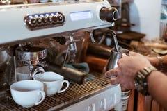 Hand barista steam milk in metal mug on coffee maker. Bar stock photography