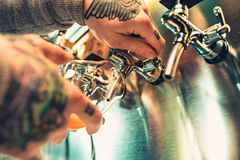 Hand of bartender pouring a large lager beer in tap. Soft, vintage instagram effect on photo. Pouring beer for client. Side view of young bartender pouring Royalty Free Stock Photography