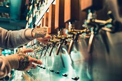 Hand of bartender pouring a large lager beer in tap. Soft, vintage instagram effect on photo. Pouring beer for client. Side view of young bartender pouring Royalty Free Stock Images