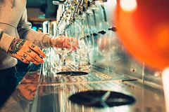Hand of bartender pouring a large lager beer in tap. Soft, vintage instagram effect on photo. Pouring beer for client. Side view of young bartender pouring Royalty Free Stock Image