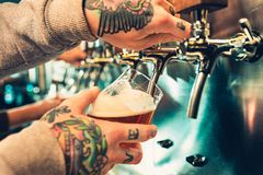 Hand of bartender pouring a large lager beer in tap. Soft, vintage instagram effect on photo. Pouring beer for client. Side view of young bartender pouring Stock Photo