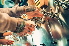 Hand of bartender pouring a large lager beer in tap. Soft, vintage instagram effect on photo. Pouring beer for client. Side view of young bartender pouring Royalty Free Stock Photo