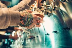 Hand of bartender pouring a large lager beer in tap. Soft, vintage instagram effect on photo. Pouring beer for client. Side view of young bartender pouring Stock Images