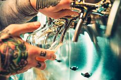 Hand of bartender pouring a large lager beer in tap. Soft, vintage instagram effect on photo. Pouring beer for client. Side view of young bartender pouring Stock Image