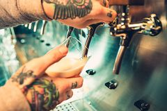 Hand of bartender pouring a large lager beer in tap. Soft, vintage instagram effect on photo. Pouring beer for client. e view of young bartender pouring beer Royalty Free Stock Photos