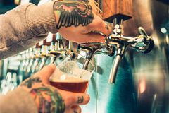 Hand of bartender pouring a large lager beer in tap. Soft, vintage instagram effect on photo. Pouring beer for client. e view of young bartender pouring beer Stock Photo