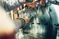 Hand of bartender pouring a large lager beer in tap. Soft, vintage instagram effect on photo. Pouring beer for client. e view of young bartender pouring beer Royalty Free Stock Photography