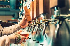 Hand of bartender pouring a large lager beer in tap. Soft, vintage instagram effect on photo. Pouring beer for client. e view of young bartender pouring beer Royalty Free Stock Images