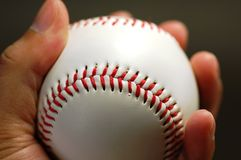 Hand and Baseball. Hand holding baseball, isolated at black background Royalty Free Stock Images