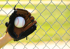 Hand of Baseball Player with Glove and Ball over Field Royalty Free Stock Photography