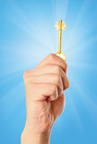 Hand with a beaming key against the sky Stock Images