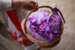 Hand with beautiful bouquet of freesias in basket, purple petals Royalty Free Stock Images