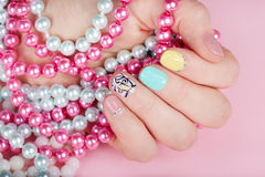 Hand with beautiful manicured nails holding colorful necklaces. Hand with beautiful manicured nails different colored with nail polish holding colorful necklaces Royalty Free Stock Images
