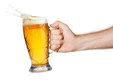 Hand with beer. Hand with mug of splashing beer isolated on white background. Male hand holding mug of light beer toasting. Hand making toast stock image
