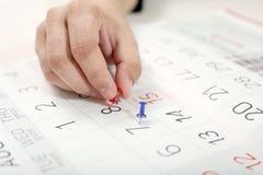 Hand befestigt Stift vom Kalender stockfoto
